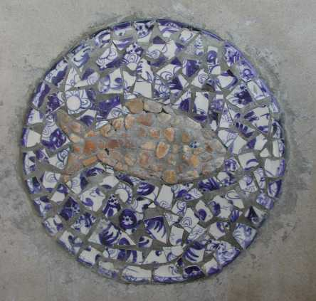 A detail of ceramic plate fragments and river rocks forming a pertinent symbol