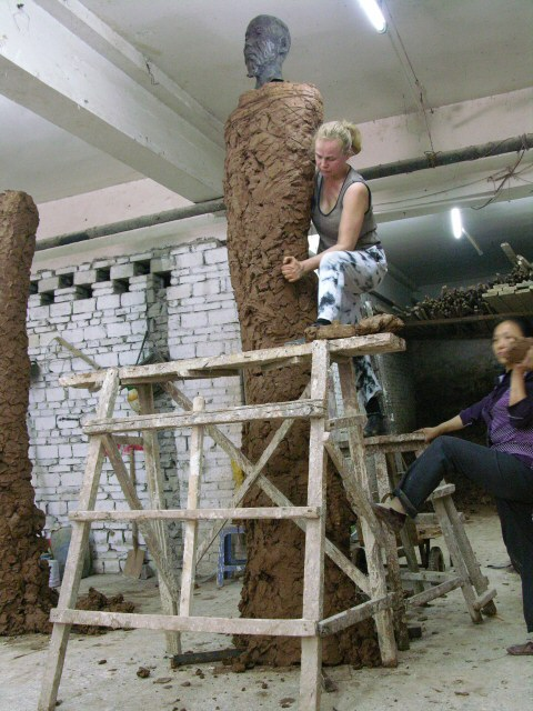 Monumental sculptor Laury Dizengremel working on one a monumental statue in clay